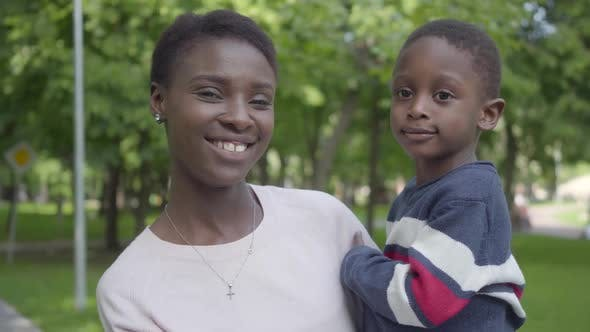 Thumbnail for Portrait of Adorable African American Woman Holding Her Funny Son in Her Arms in the Green Park