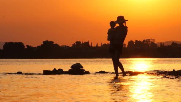Thumbnail for Happy Mother on Maternity Leave on Seascape Background. Beautiful Mother Holding Her Daughter Up in