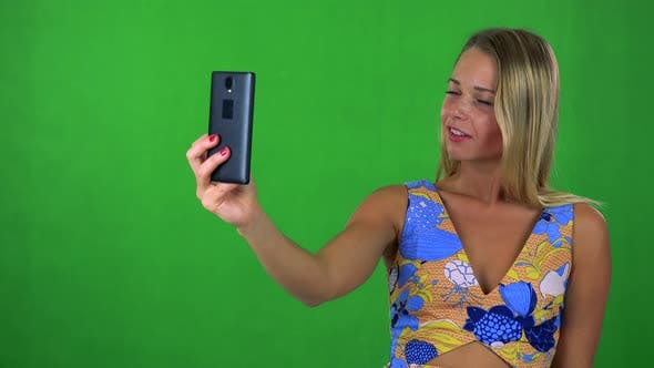 Thumbnail for Young Pretty Blond Woman Photographs with Smartphone (Selfie) - Green Screen - Studio