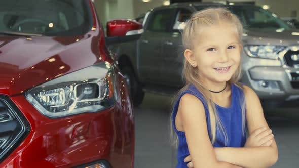 Thumbnail for A Sweet Girl Stands on the Background of the Car and Laughs