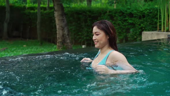 slow-motion of young woman enjoying and walking in swimming pool