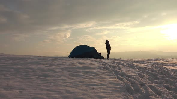 Hiker drink tea from thermos in front of tent, at sunset