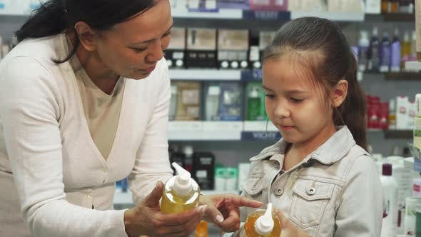 Thumbnail for A Girl with Her Daughter Chooses Tubes of Cosmetic in a Pharmacy