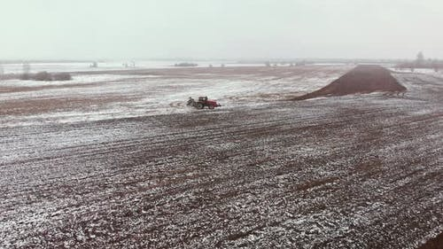 Tractor Plows Snowcovered Farmland in Spring
