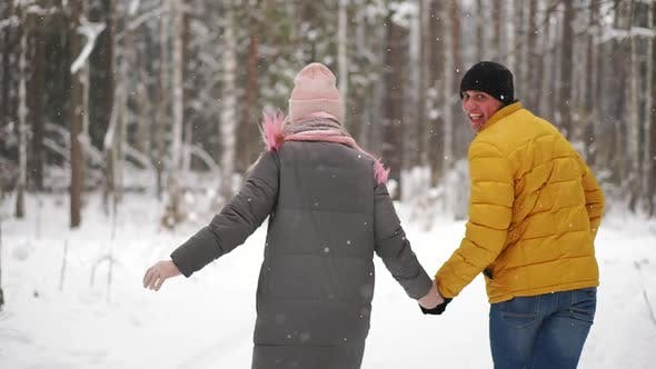 Cover Image for A Young and Beautiful Couple Is Having Fun in the Park, Running and Holding Hands. Valentine's Day