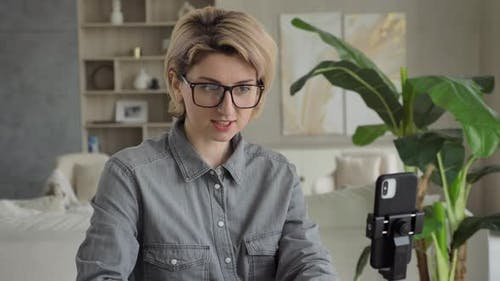 Blonde Blogger in Glasses Talks Sitting at Black Smartphone