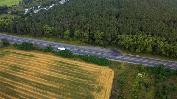 Cover Image for White Truck Rides on the Highway Among a Dense Forest, Traveling on the Forest Asphalt Road Aerial