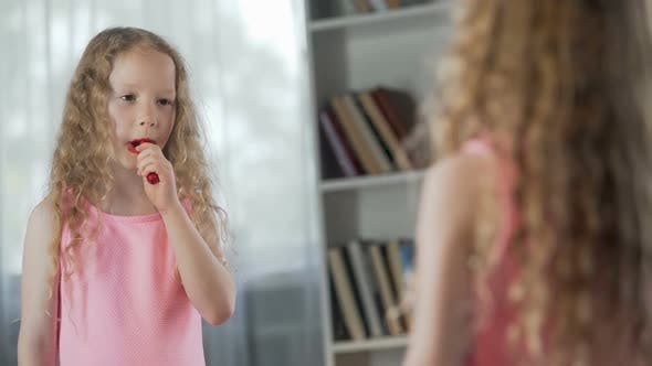Cover Image for Little Girl Putting on First Make-Up, Playing with Lipstick in Front of Mirror