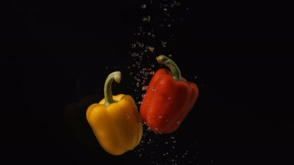 Thumbnail for Red and Yellow Peppers Falling Into Water with Bubbles on Black Background. Vegetables Falling Into
