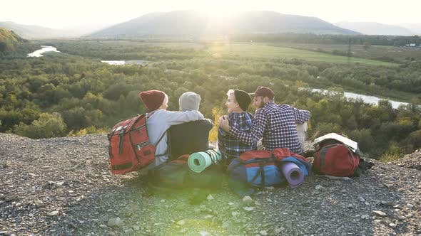 Group of Four Friends Sitting on the Ground in the Mountain