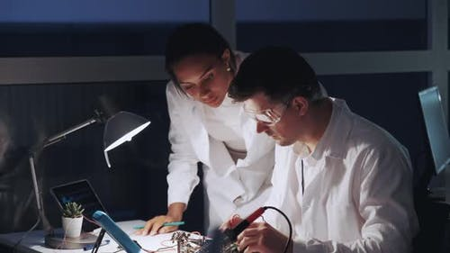 Two Mixed Race Electronics Engineers Working with Multimeter Tester and Other Electronic Devices