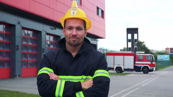 Thumbnail for A Firefighter Looks at the Camera with Arms Folded Across Chest - a Truck Drives Into a Fire Station