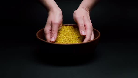 Taking Bulgur in Hands From Bowl on Black Background