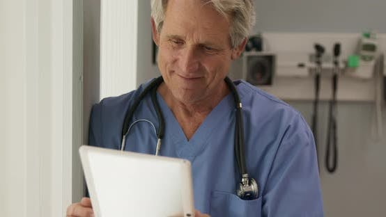 Thumbnail for Happy Senior Caucasian male doctor reading positive test results and smiling