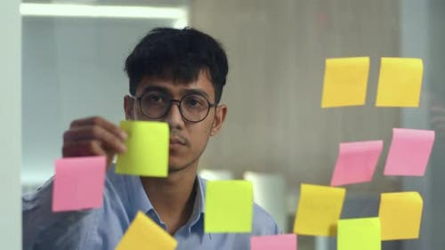 Young professional business male write information, strategy, reminder on paper at office.