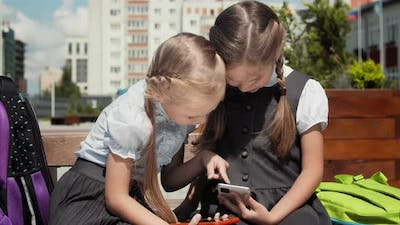 Children Play With Mobile Phone In Schoolyard