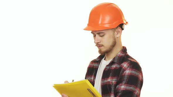 Cover Image for Young Professional Male Contractor in Hardhat Making Notes Smiling