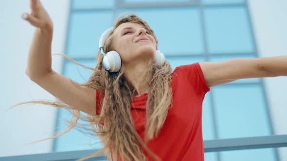 A Young Girl in Headphones is Listening to Music and Amusingly Dancing on a City Background