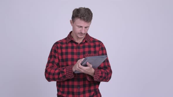 Thumbnail for Happy Bearded Hipster Man Thinking While Using Digital Tablet