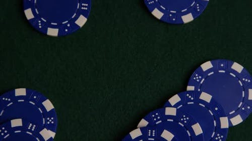 Rotating shot of poker cards and poker chips on a green felt surface - POKER 035