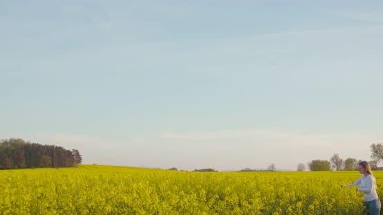 Female Farmer Examining Oilseed Rape Field
