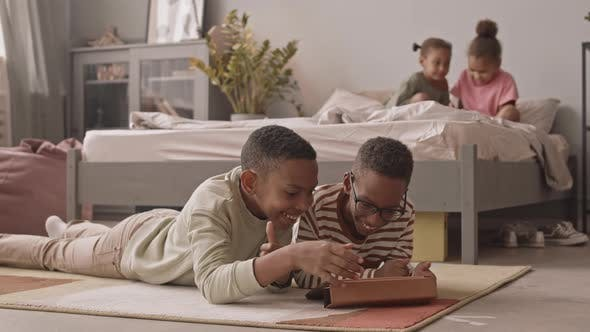 African American Schoolchildren with Gadgets at Home