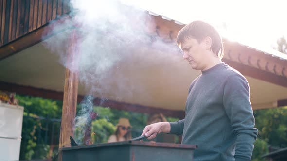 Young Man Standing Near the Summer House Prepares the Coals in the Grill The Girls Help Him