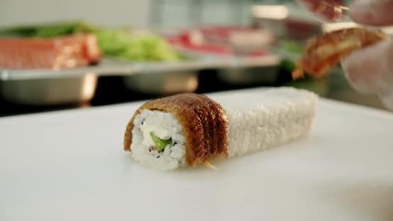 Thumbnail for Slow Motion. Sushi Master Fresh Sushi Rolls Puts Acne on Sushi. Close Up