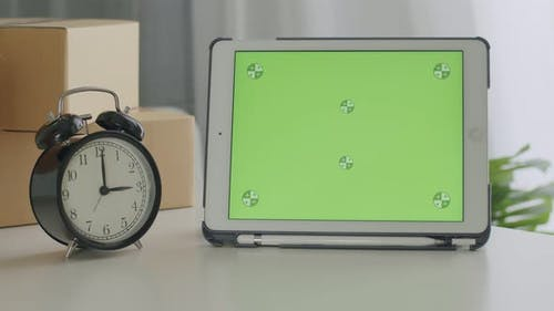 Tablet with blank green screen chroma key template on the table.