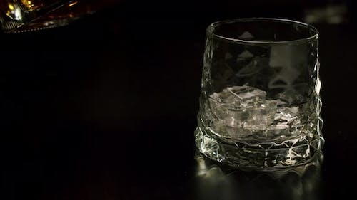 Slow Motion Golden Whiskey Pouring Glass Ice Cubes From Bottle