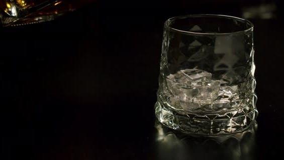 Zeitlupe Goldener Whisky, der Eiswürfel aus Glas gießt