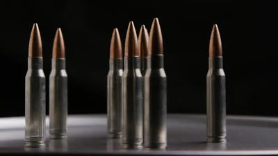Cinematic rotating shot of bullets on a metallic surface - BULLETS