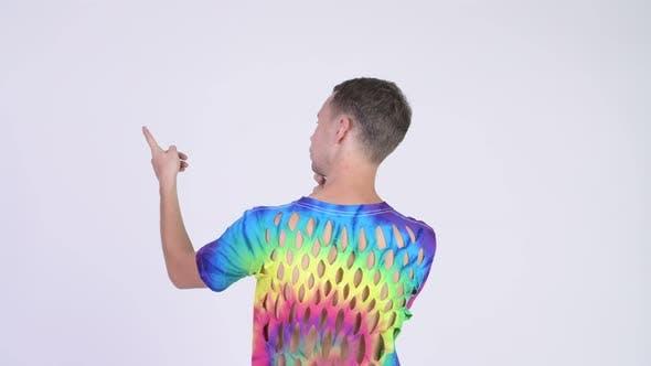 Thumbnail for Rückansicht des Mannes trägt Tie-Dye Shirt mit Löchern und Zeigefinger