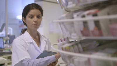 MS Female pharmacist searching medicine in pharmacy with digital tablet