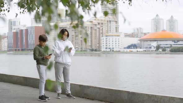 Thumbnail for Asian Mother and Son Using Smartphone and Running Outdoors