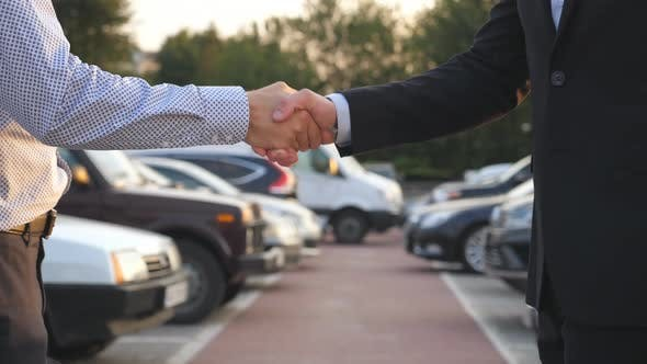 Thumbnail for Male Hands in Suit Giving Keys of Car To His Friend. Arm of Businessman Passes Car Key. Handshake