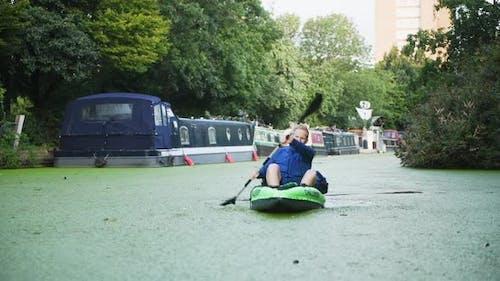 A man kayaking towards camera urban setting