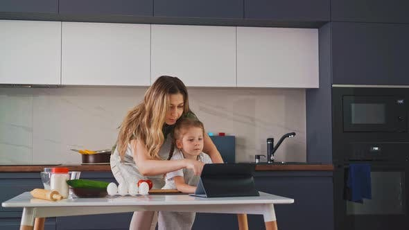 Woman with Daughter Looks for Recipes with Tablet in Kitchen