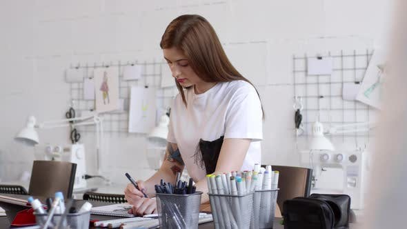 Young Beautiful Woman Drawing Sketch of Female Dress in Sewing Studio