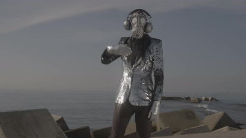 Man with Sparkling Gas Mask Dancing By the Sea