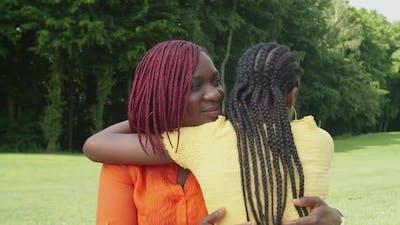 Affectionate Black Mother Hugging Teenage Daughter Outdoors