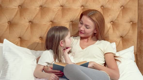 Thumbnail for Attractive Woman Enjoying Reading a Book with Her Adorable Little Daughter