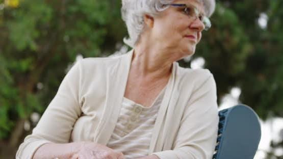 Elderly woman sitting on park bench thinking