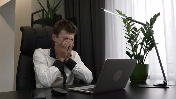 Tired overworked man is rubbing eyes in business office.