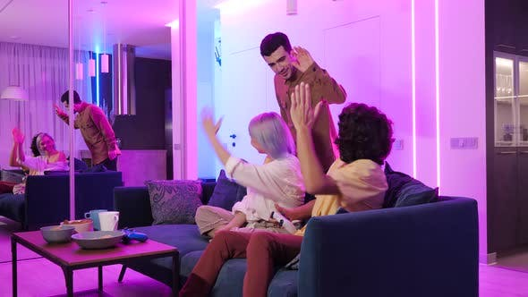 Thumbnail for Young Man Coming To Friends To Play Games on Gaming Console in Neon Color Room