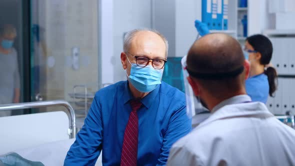 Physician Talking with Patient in Mask