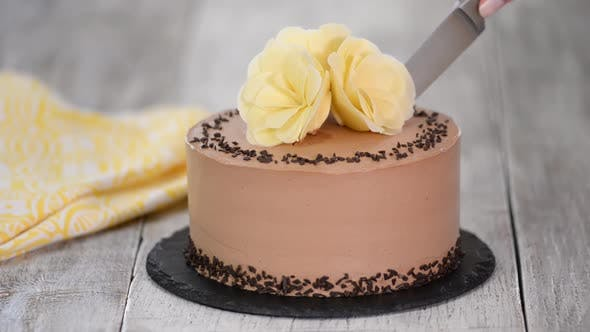 Thumbnail for Cutting of chocolate cake on plate. Chocolate cake decorated white chocolate flowers.