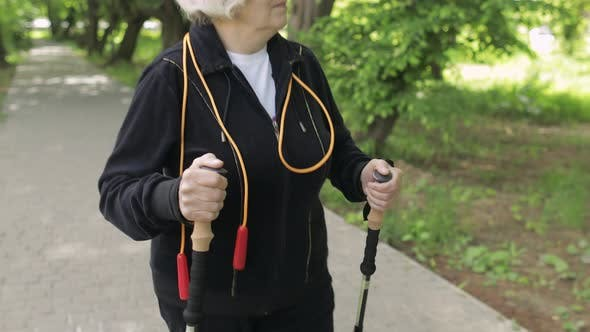 Active Senior Old Woman Training Nordic Walking with Ski Trekking Poles in Park