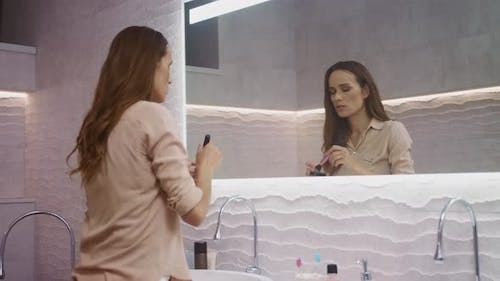 Beauty Woman Doing Makeup in Bathroom. Happy Woman Making Morning Makeup.