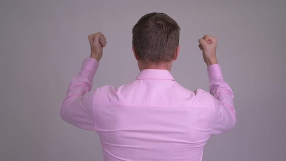 Cover Image for Rear View of Young Businessman Looking Excited with Fists Raised